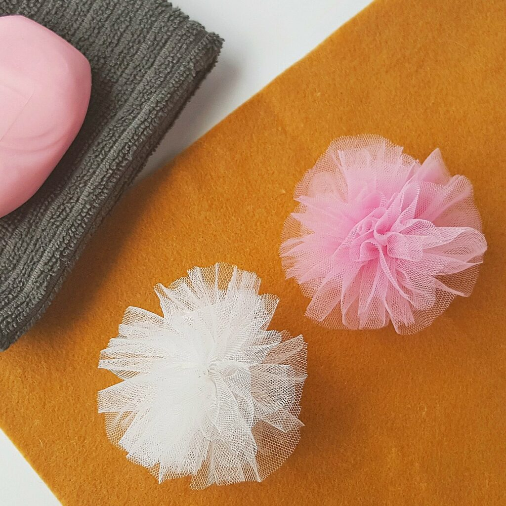 white and pink bath scrubbies on yellow felt against grey washcloth with pink soap bar