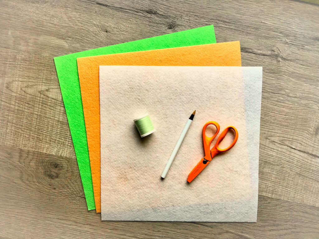 three pieces of felt with thread and scissors