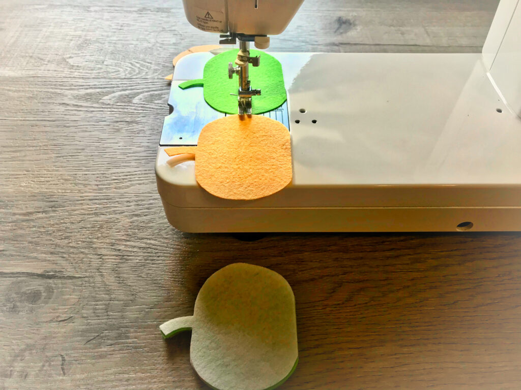 sewing felt pumpkins together on a sewing machine