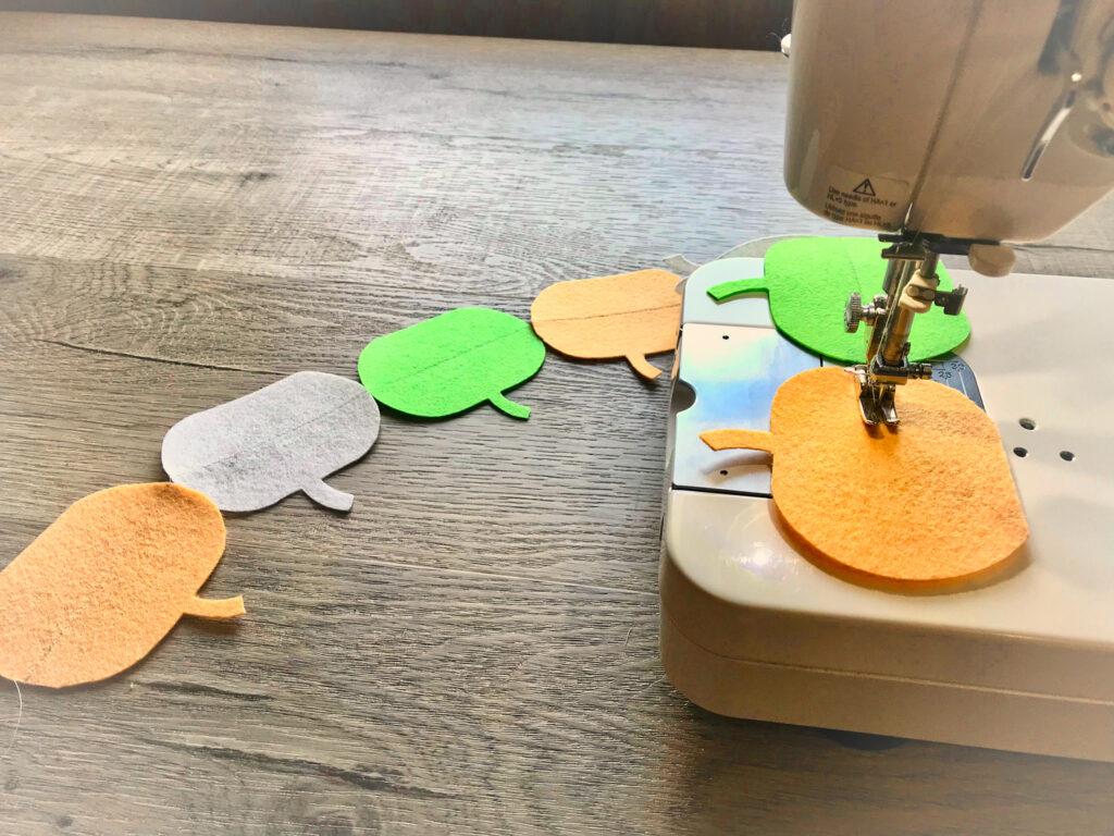sewing felt pumpkin garland on a sewing machine