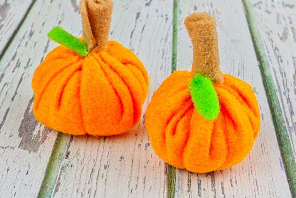 mini felt pumpkins with green leaves on table