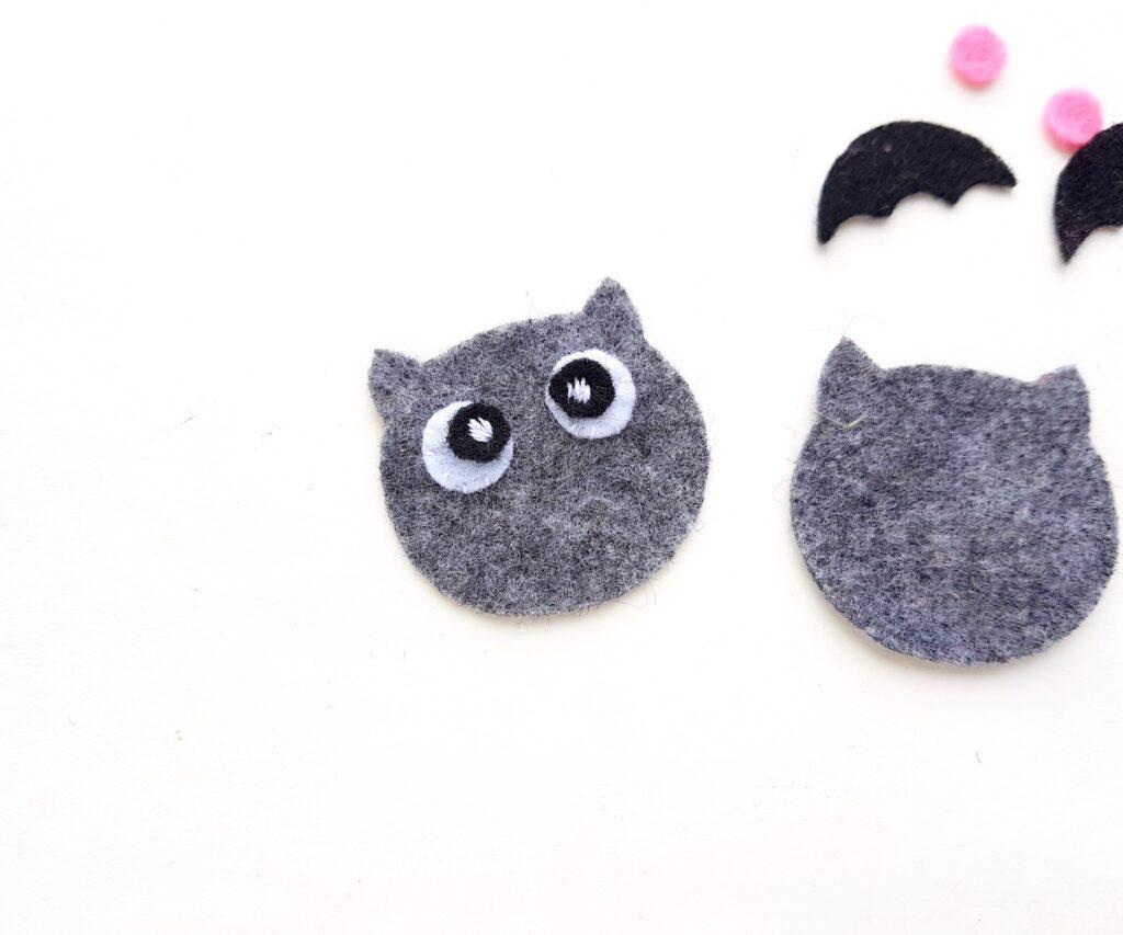 applying facial features to grey felt plush bat doll