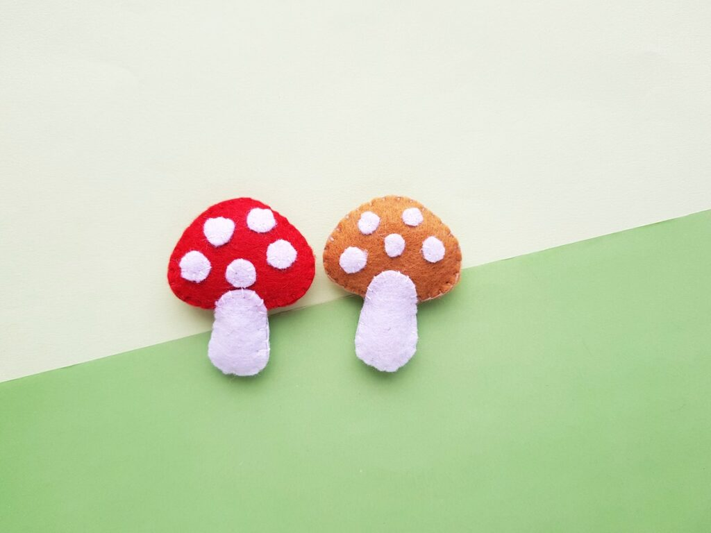 Felt Mushroom Plush completed side by side on green background