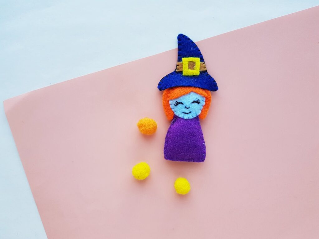 Witch Plush Doll completed with yellow pom poms on table