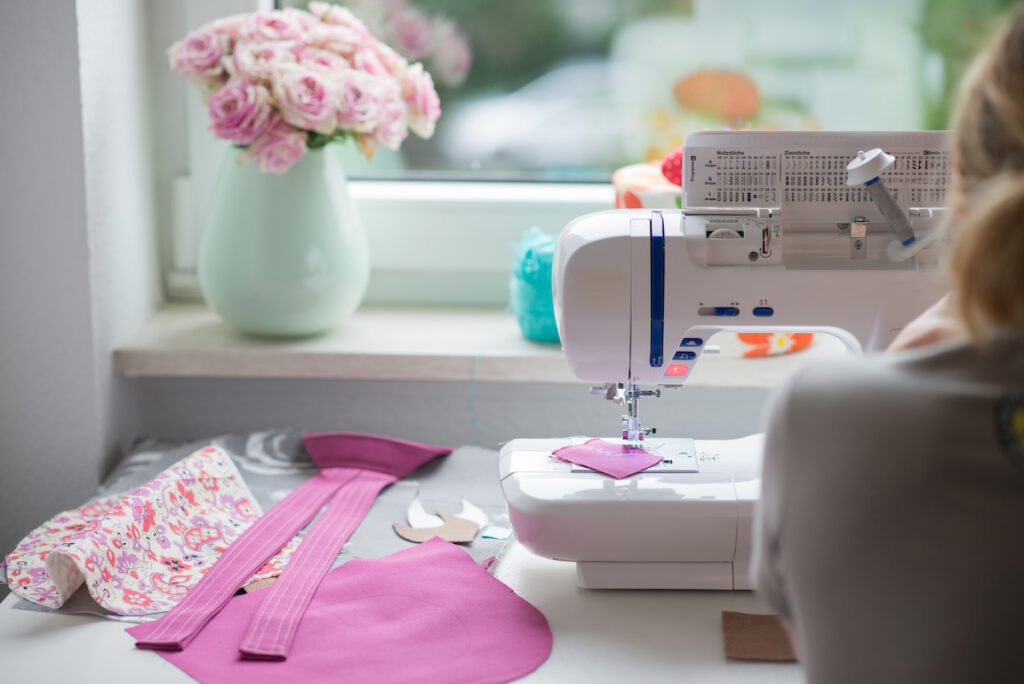 view of sewing room with sewing machine, fabric, flowers and woman