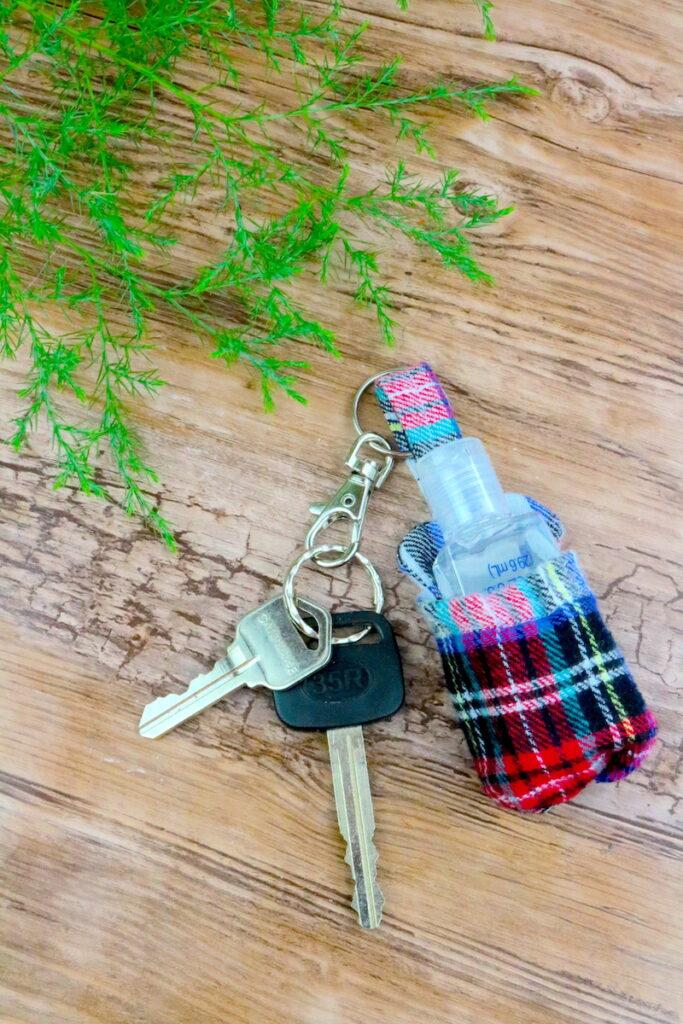 DIY hand sanitizer holder keychain on wood table