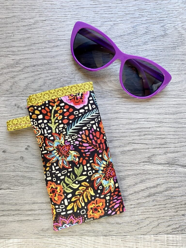Sunglasses Case on table with pink sunglasses