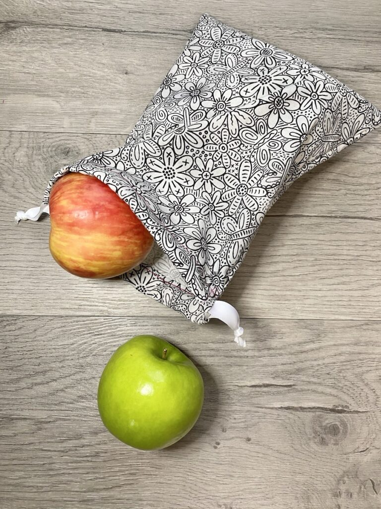 sewing a drawstring bag on wood background