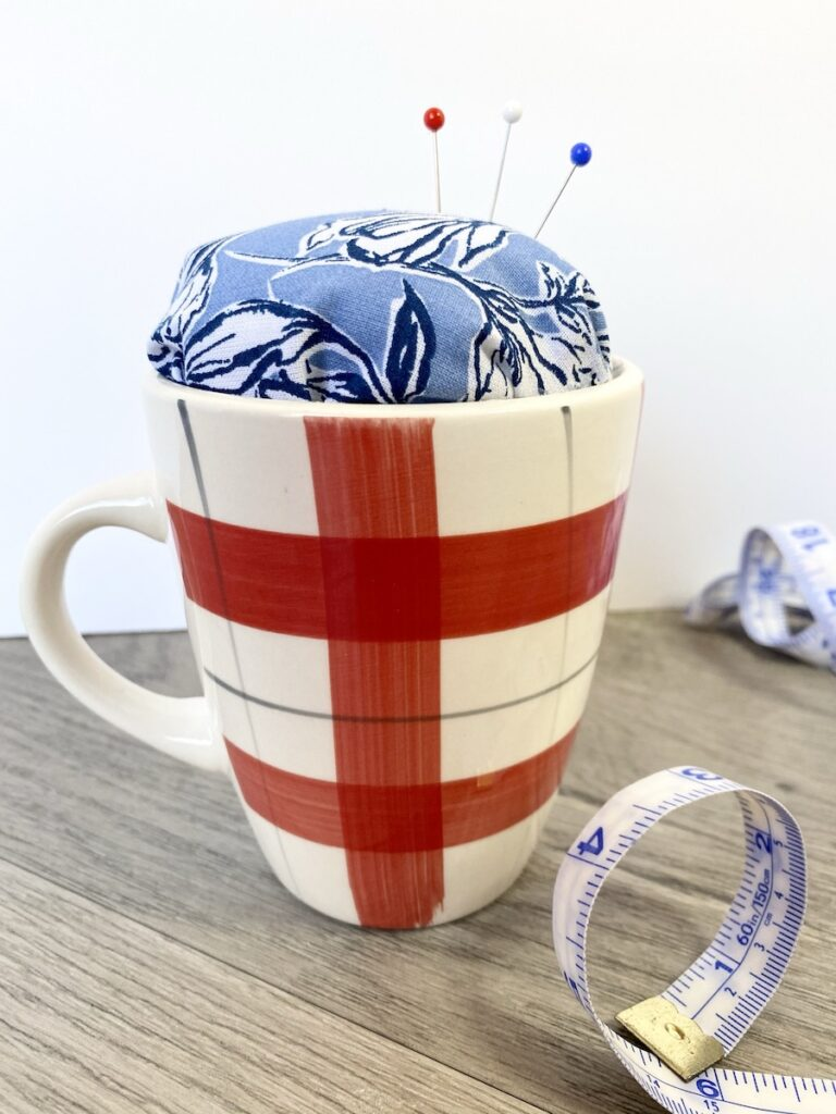 teacup pin cushion with ribbon on table