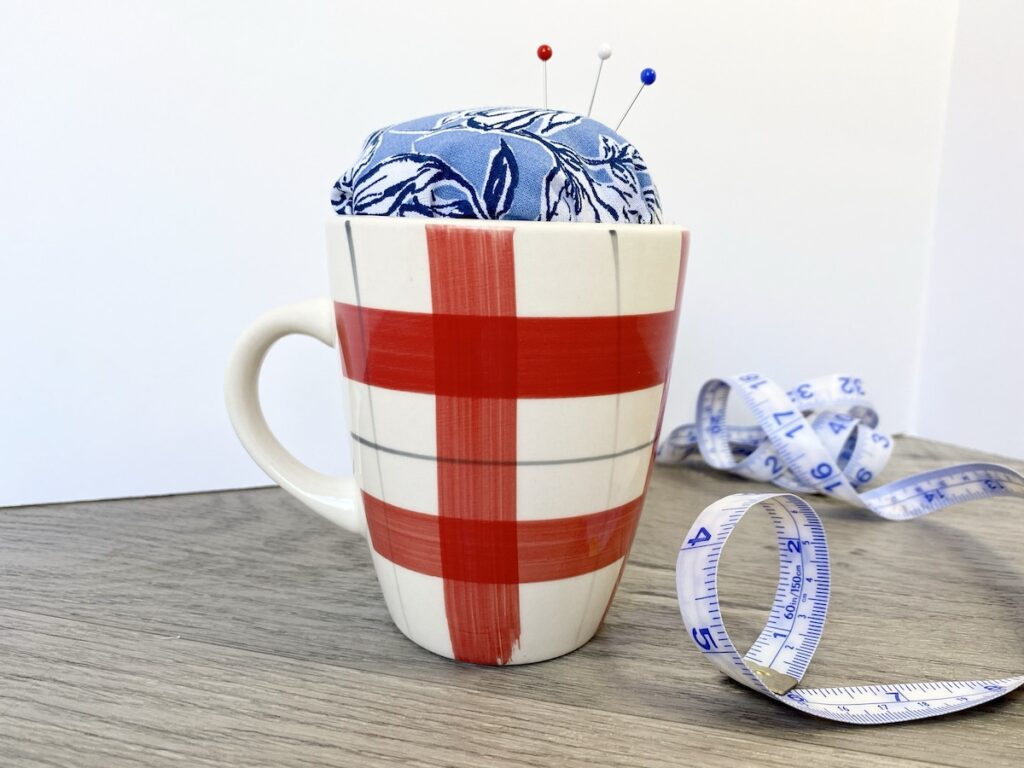 teacup pin cushion in mug on desk