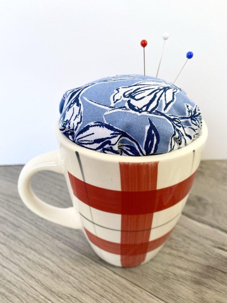 teacup pin cushion closeup on table
