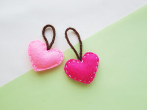 pink felt heart plushies on green background